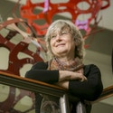 Duke mathematician and professor of electrical and computer engineering Ingrid Daubechies in the Fitzpatrick Center for Interdisciplinary Engineering Medicine and Applied Sciences (F-CIEMAS) atrium with two of the metallic orb sculptures that are part of installation by designer George Hart that were commissioned by Daubechies