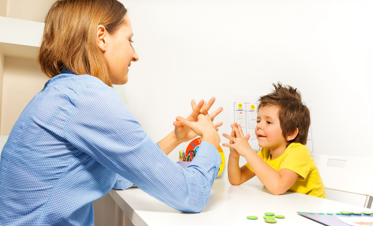 Boy exercises by putting hands and fingers together with therapist showing it improving motor skills sitting opposite at the table indoors