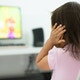 A child watching tv holding her ears because she is afraid of the sound; Child behavior theme