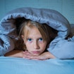 Cute little caucasian girl lying in bed covering her head with blanket feeling exhausted and sleepless suffering from insomnia Depression Stress in Children Emotional and Sleeping Disorders concept.